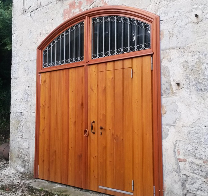 Porte massive en Mélèze avec traverse cintrée et grille forgée