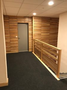 Habillages muraux acoustique en Frêne finition vernis en atelier